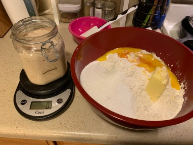 jar with starter on a kitchen scale. bowl with flour, sugar, butter, salt, and eggs next to it on the counter.