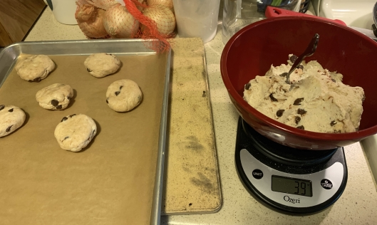 bowl of dough on a scale next to a baking sheet with portioned out dough