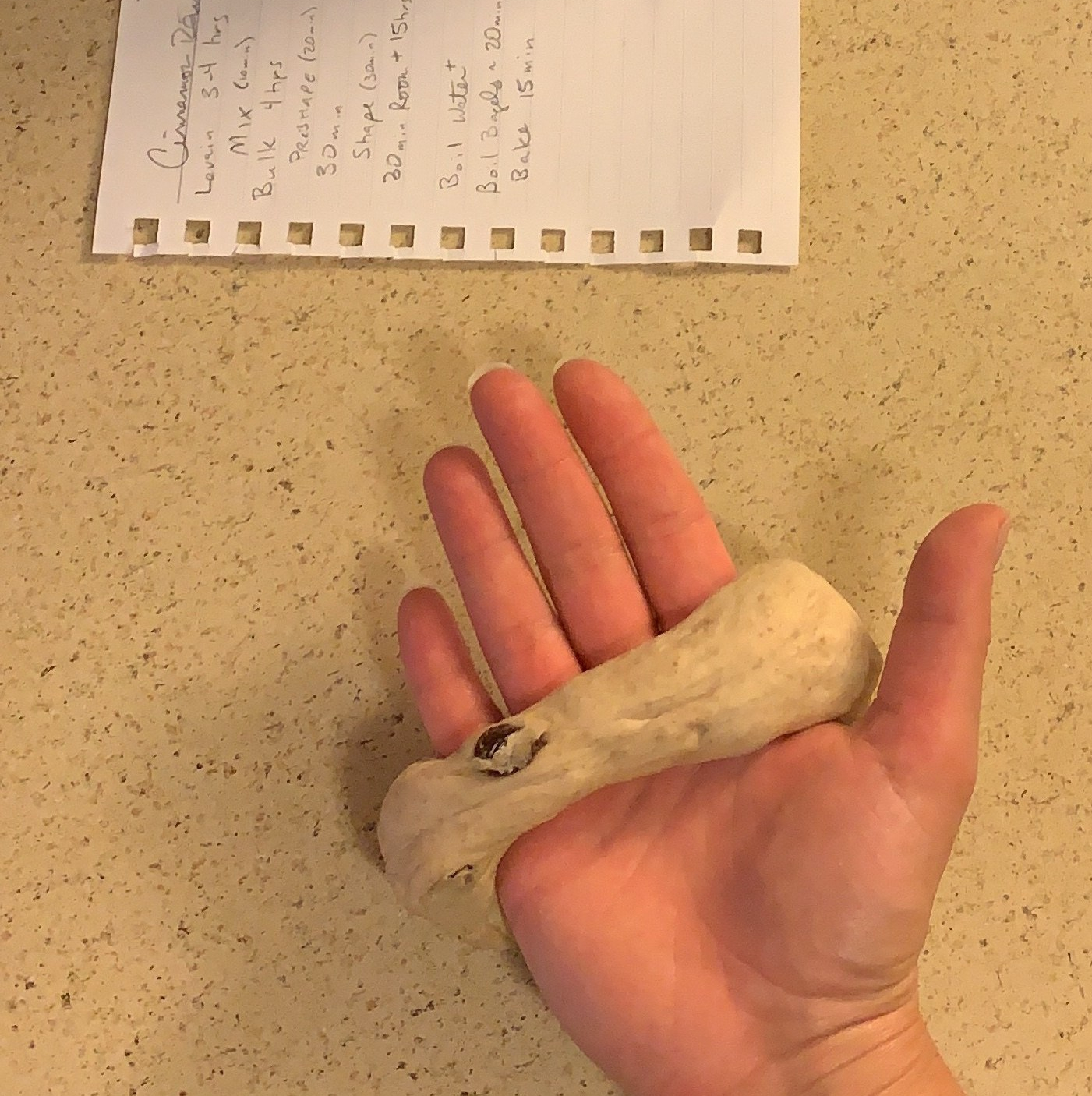 hand with bagel dough wrapped around the palm, next to a piece of notebook paper on the counter