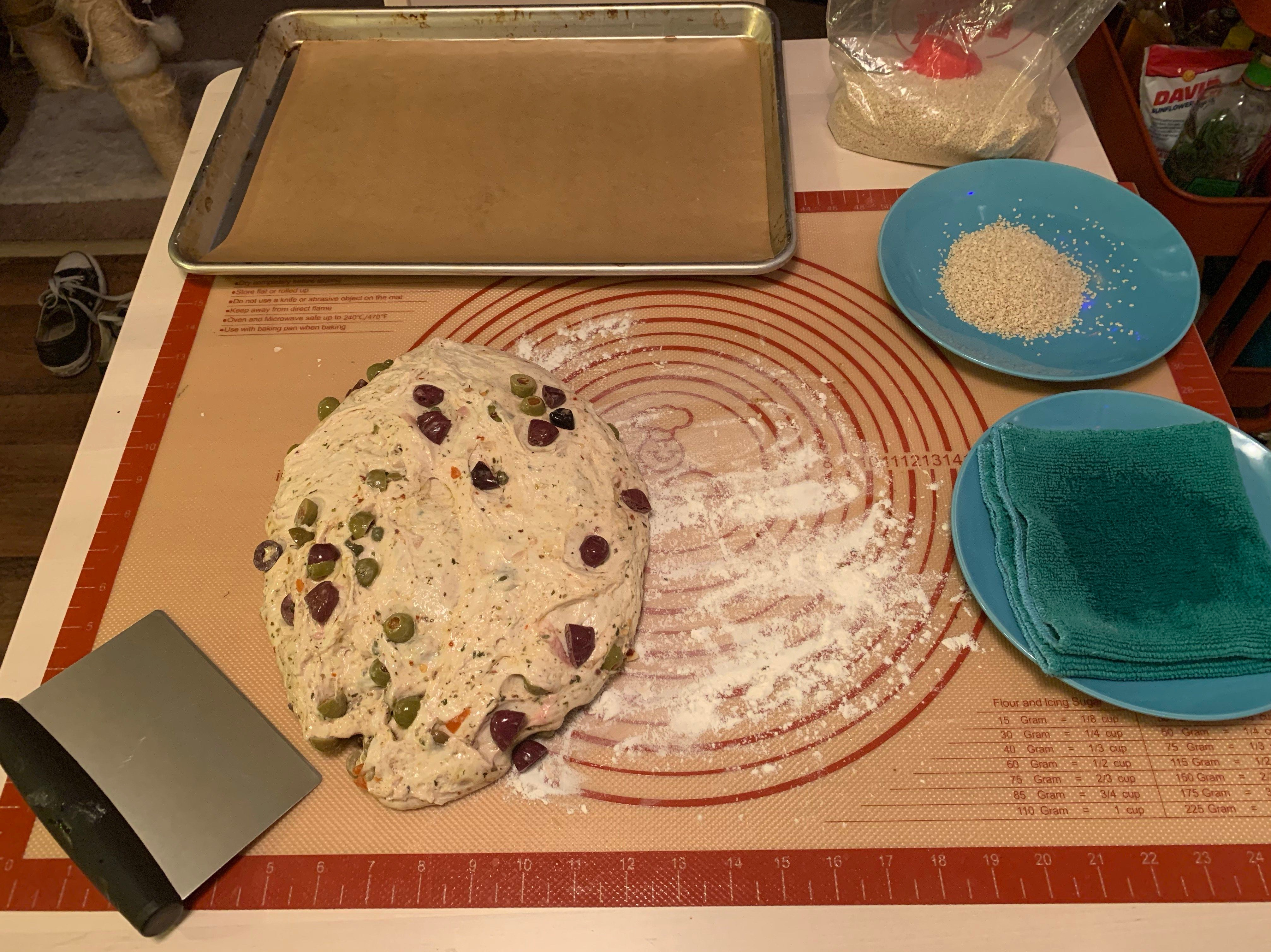 Table set up to shape rolls. Top right is a baking sheet with parchment paper. To the right is a bag full of sesame seeds with a measuring cup inside. Bottom half of table has a rubber mat. On the bottom left of the mat is a bench scraper. next to it is the fully bulked olive dough. Bottom right of the mat is a blue plate with a green towel on it; the towel is soaked in the middle with water. Above that plate is another blue plate with a pile of sesame seeds.