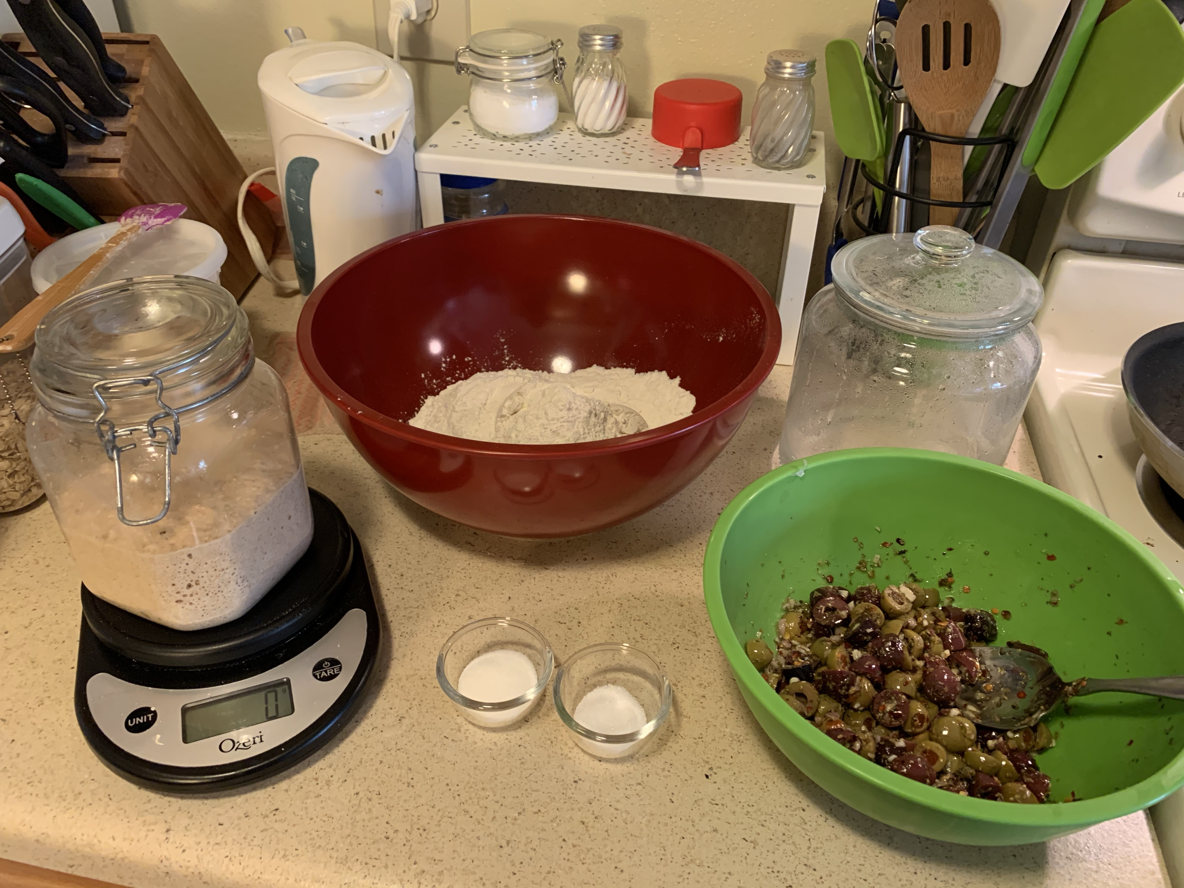 Counter with various bread ingredients, including a jar of sourdough starter on a kitchen scale, a bowl of flour, two small bowls with salt and sugar, a bowl of olive salad, and a glass jar with warm water.