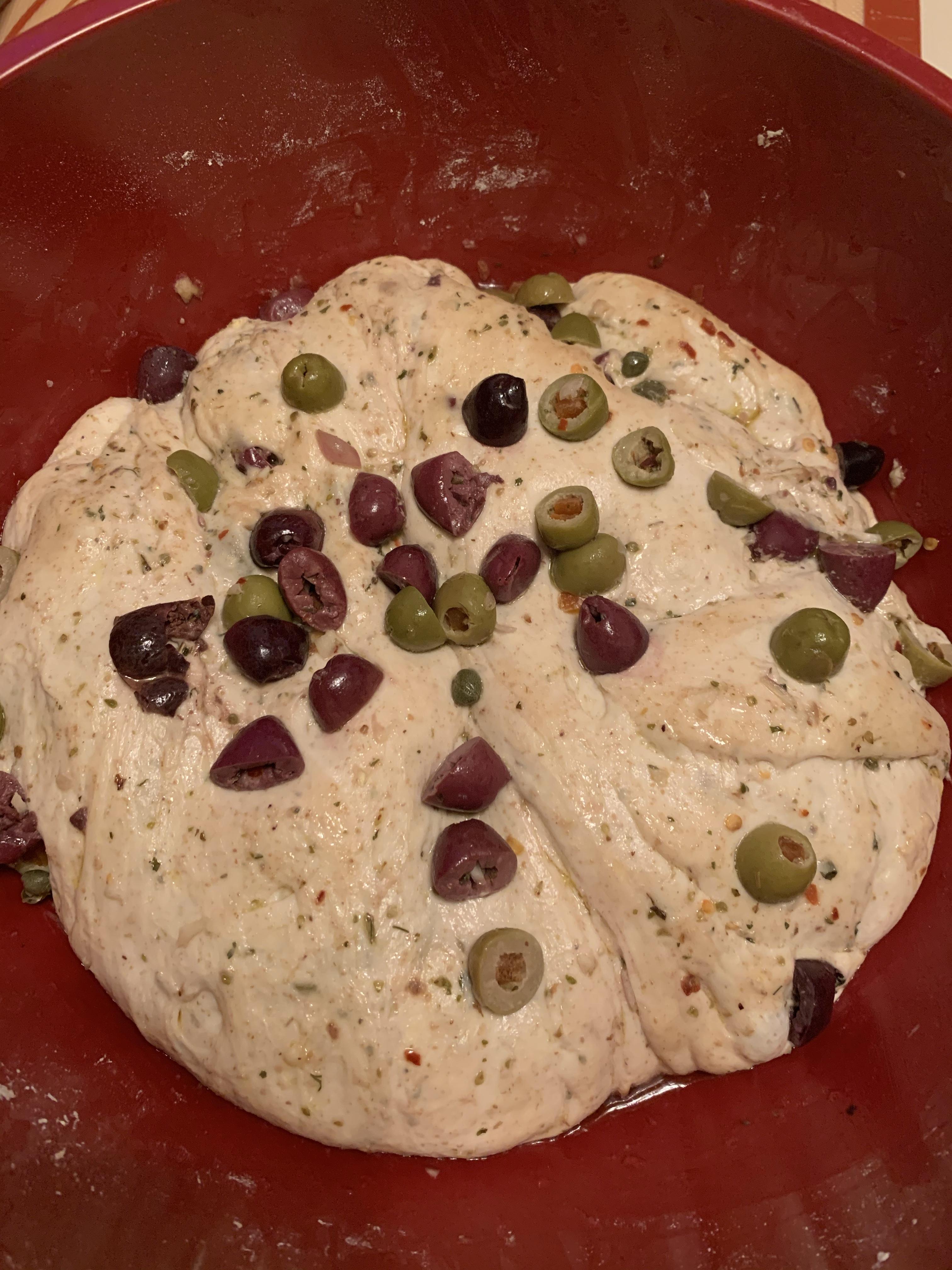 Dough, covered in olives, after bulk fermentation