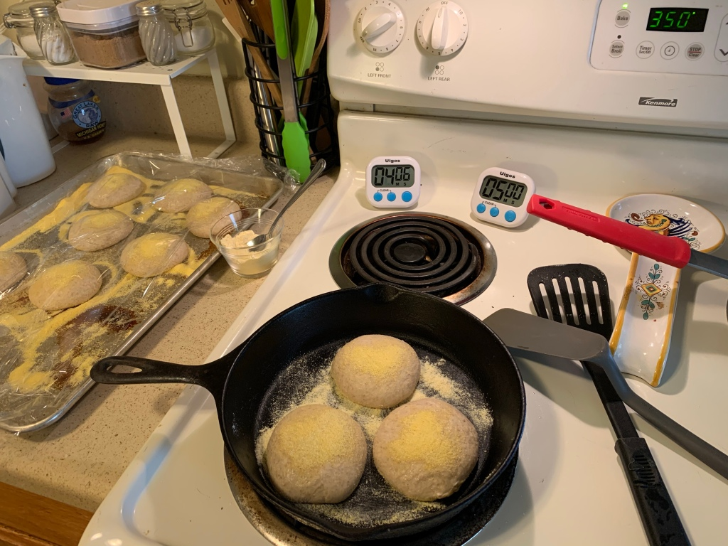On the right is the counter with a baking pan. Is has several balls of dough covered in cornmeal and plastic wrap. Next to it on the counter is a small glass bowl filled with flour and a spoon. On the front left stove burner is a skillet with three dough balls and cornmeal. The dial is set to 3. Behind the top left burner are two digital timers reading 4:06 and 5:00. Next to the burners are two spatulas and a spoon rest. The oven is set to bake at 350°.