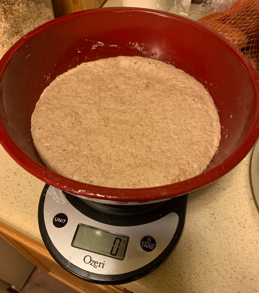 Red bowl full of mature sourdough starter on a kitchen scale reading 0g.