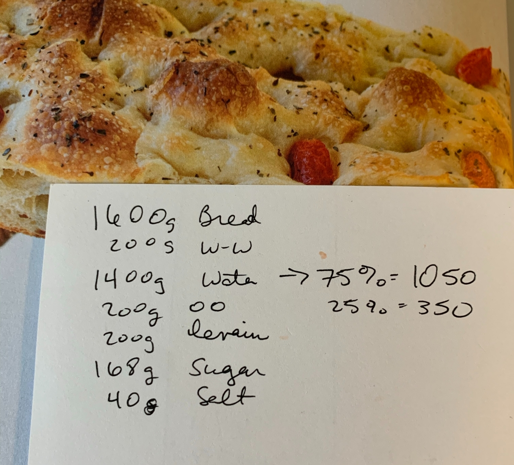 Handwritten ingredient list on top of picture of focaccia from the cookbook.