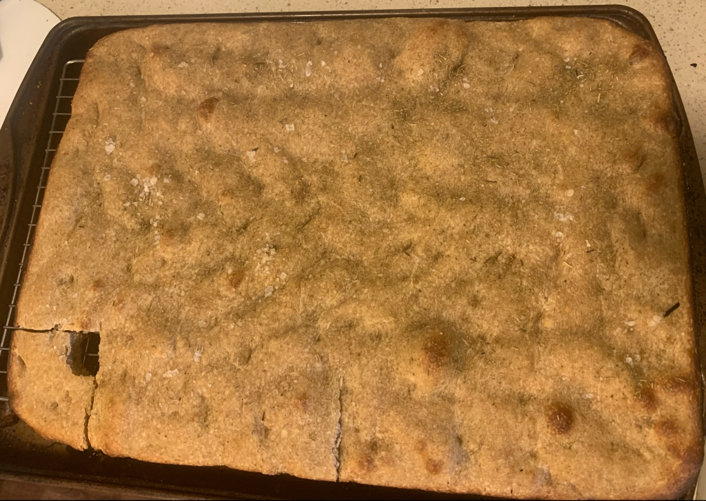 Baking sheet with boring baked bread. The bottom left corner has been cut out, a bite removed, and then replaced.