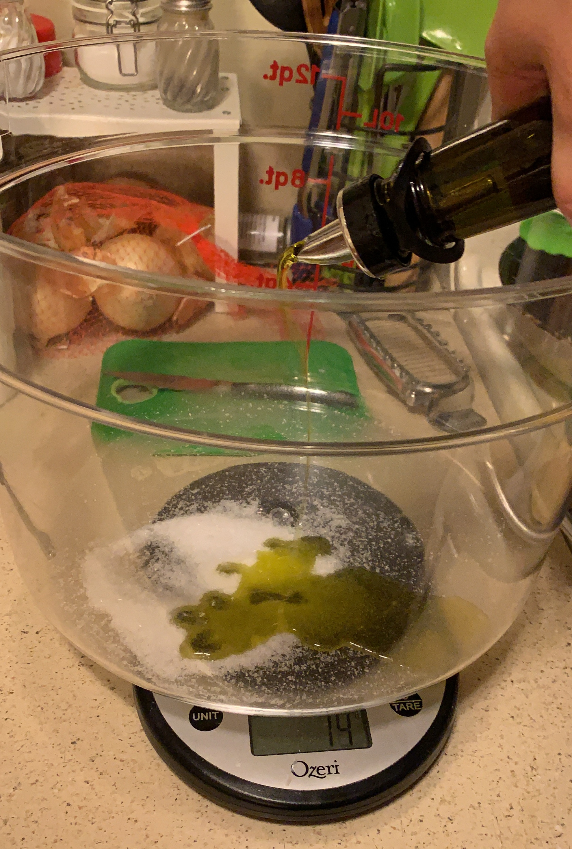Olive oil pouring into a large plastic tub with salt on kitchen scale.
