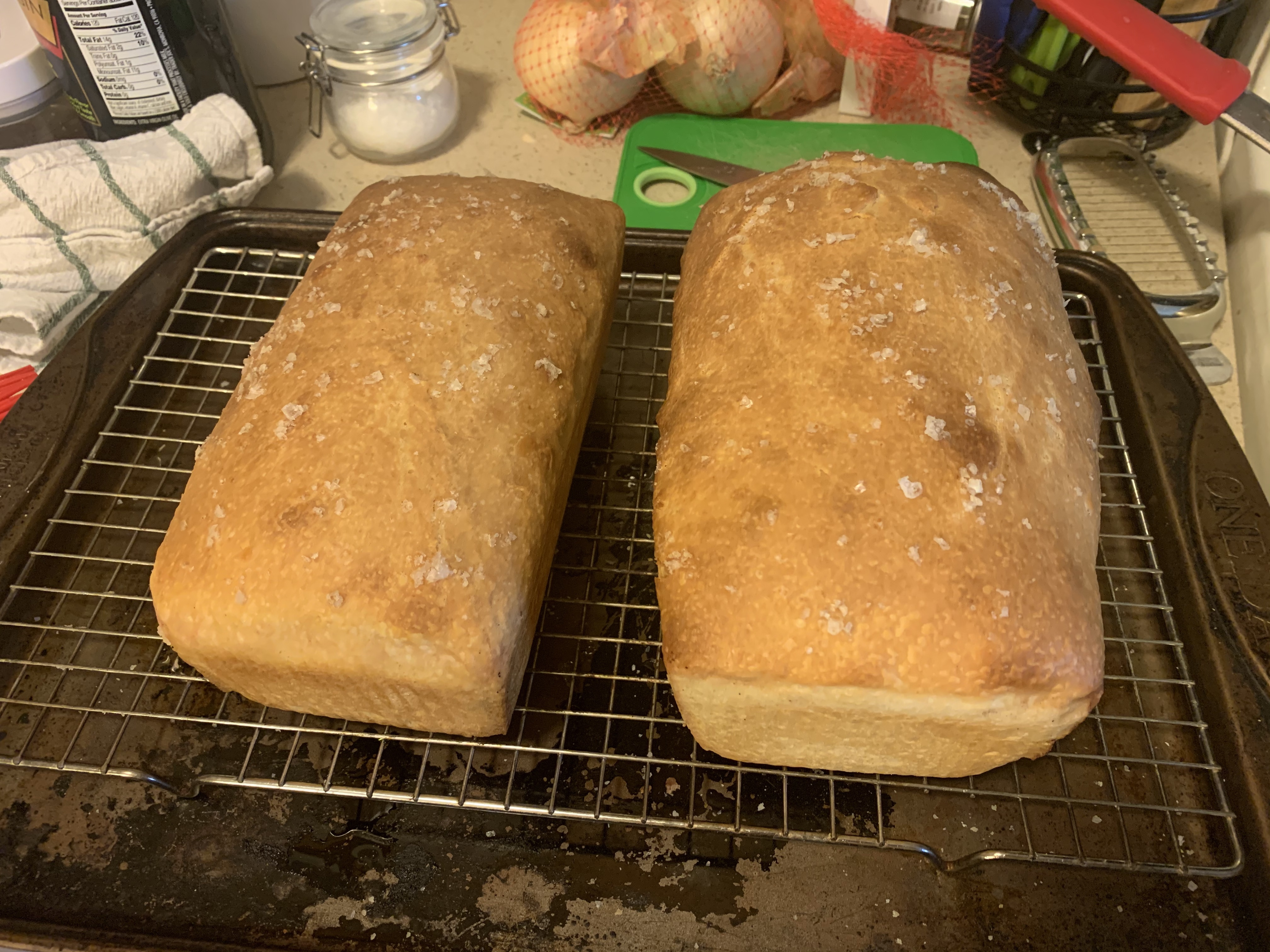 Two baked loaves, cooling on a wire rack