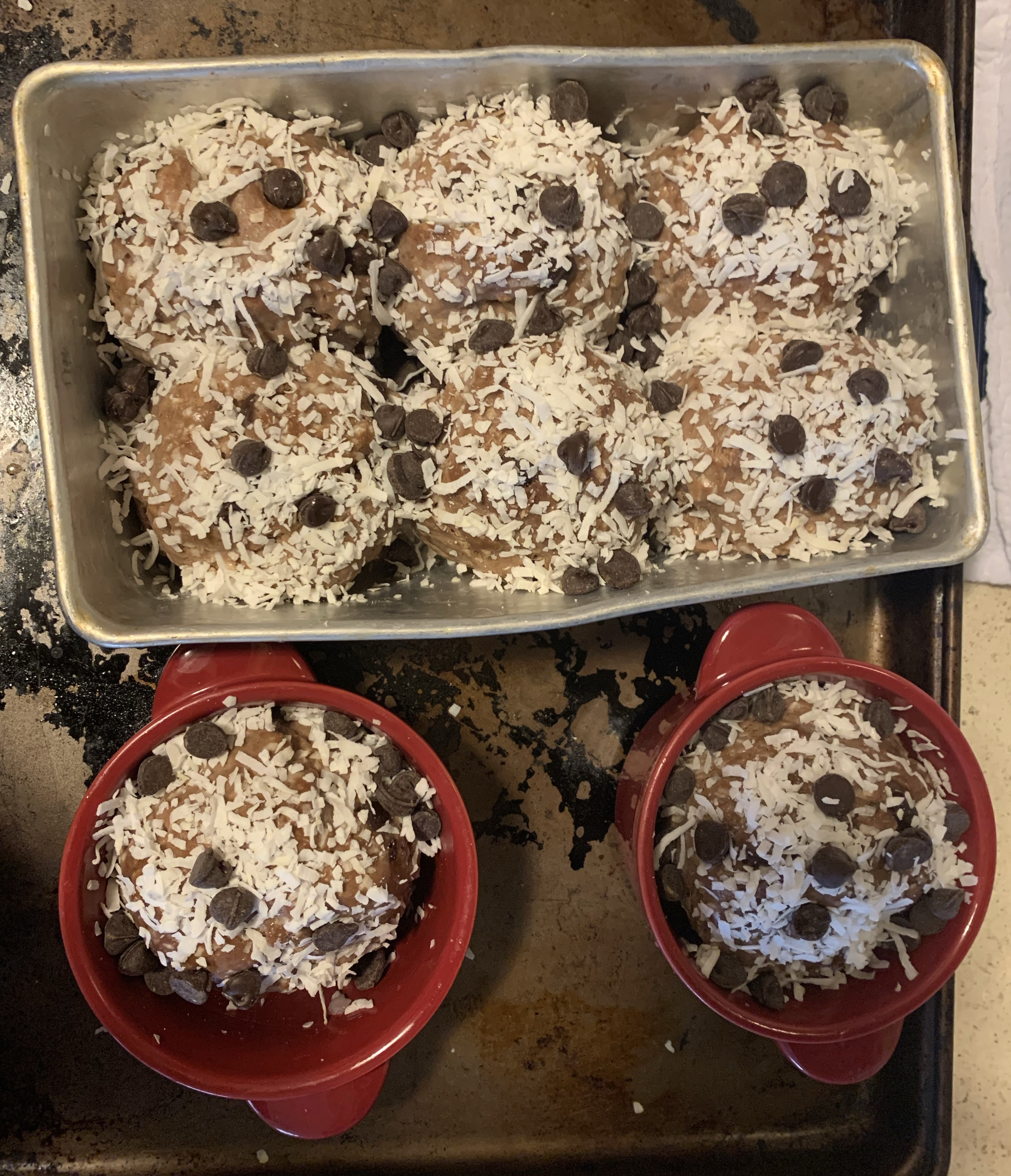 choco pan de coco covered in shredded coconut and chocolate chips, before baking