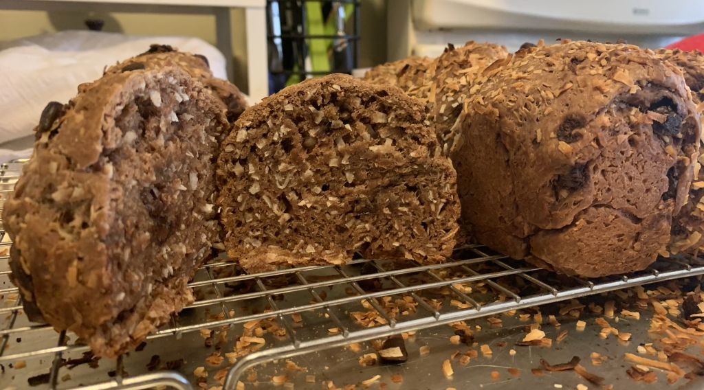 Lots of baked choco pan de coco on a wire rack. One piece is cut open and showing the crumb full of coconut bits.