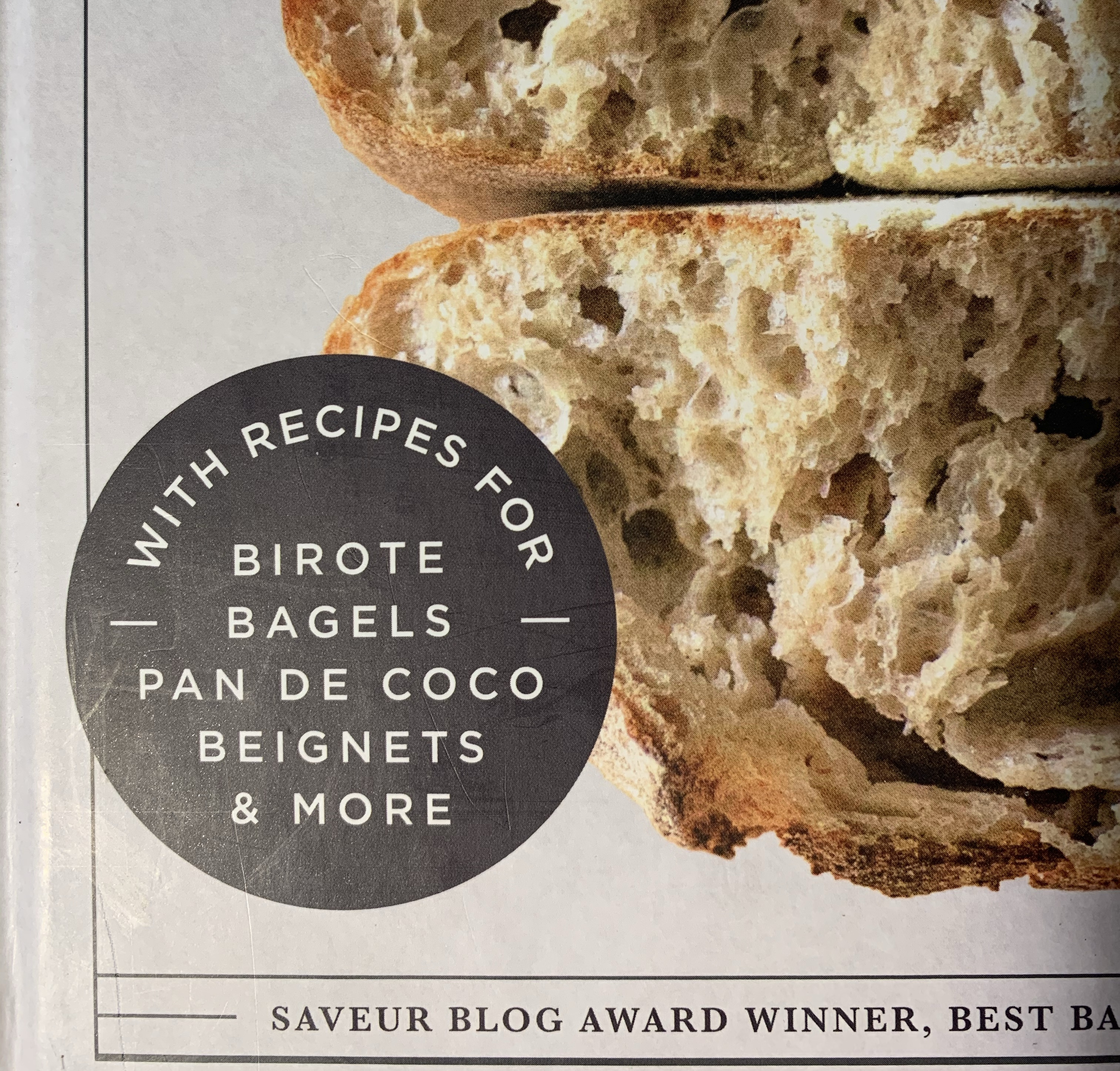 """portion of the cover of New World Sourdough. A black circle with white text that reads """"with recipes for birote bagels pan de coco beignets & more"""""""