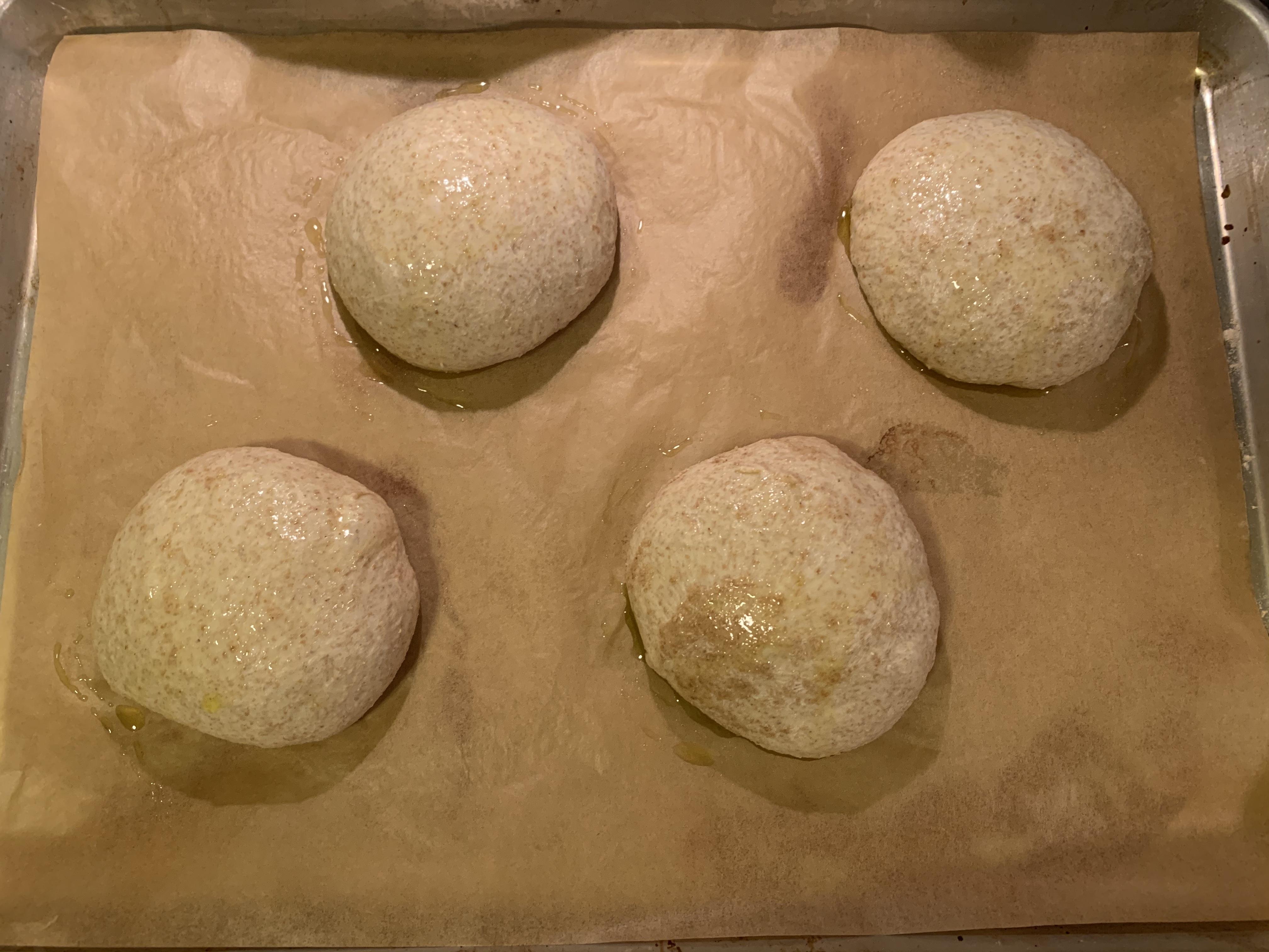 four balls of dough on parchment paper