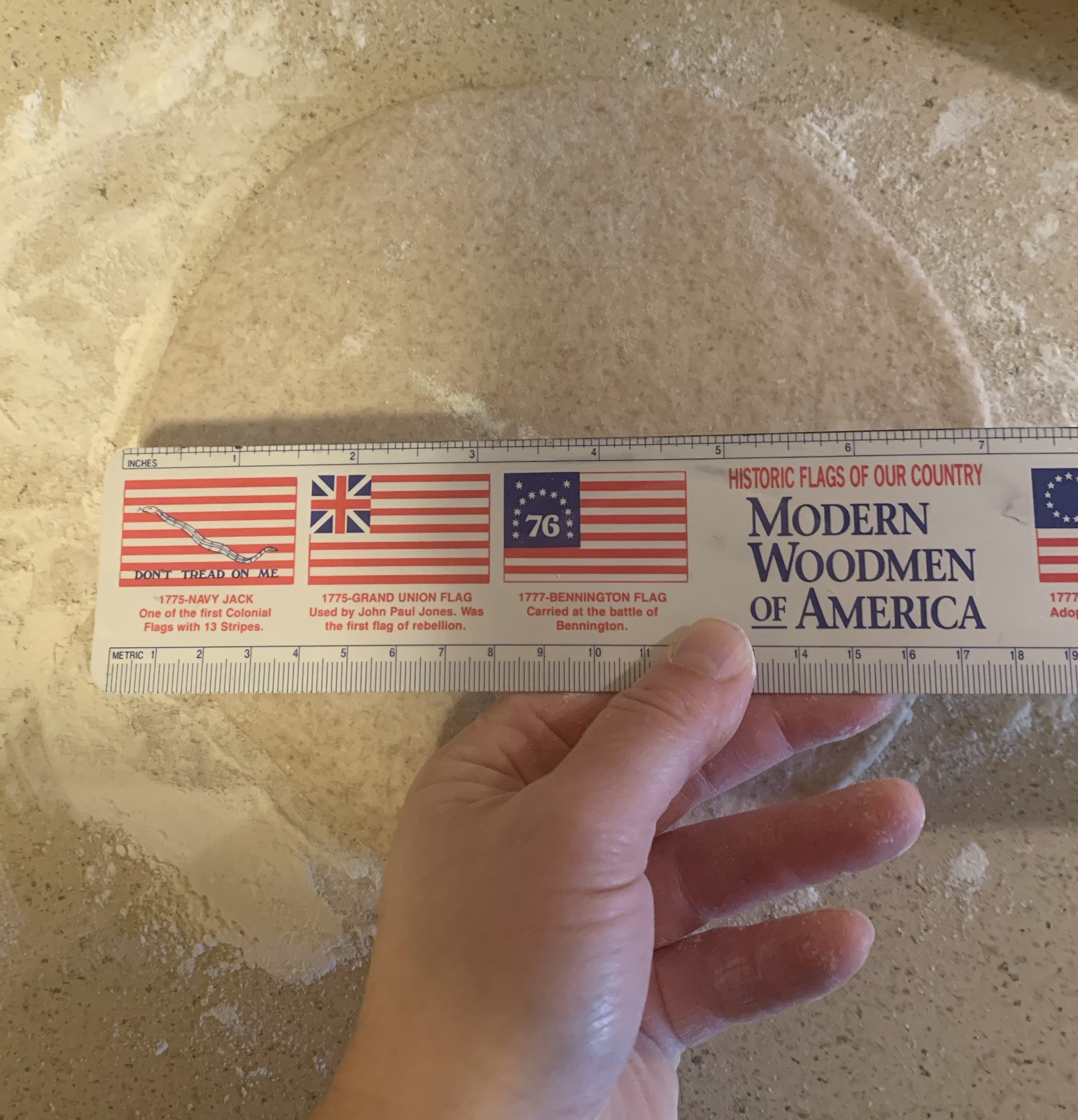 hand holding ruler over rolled out round of dough next to rolling pin