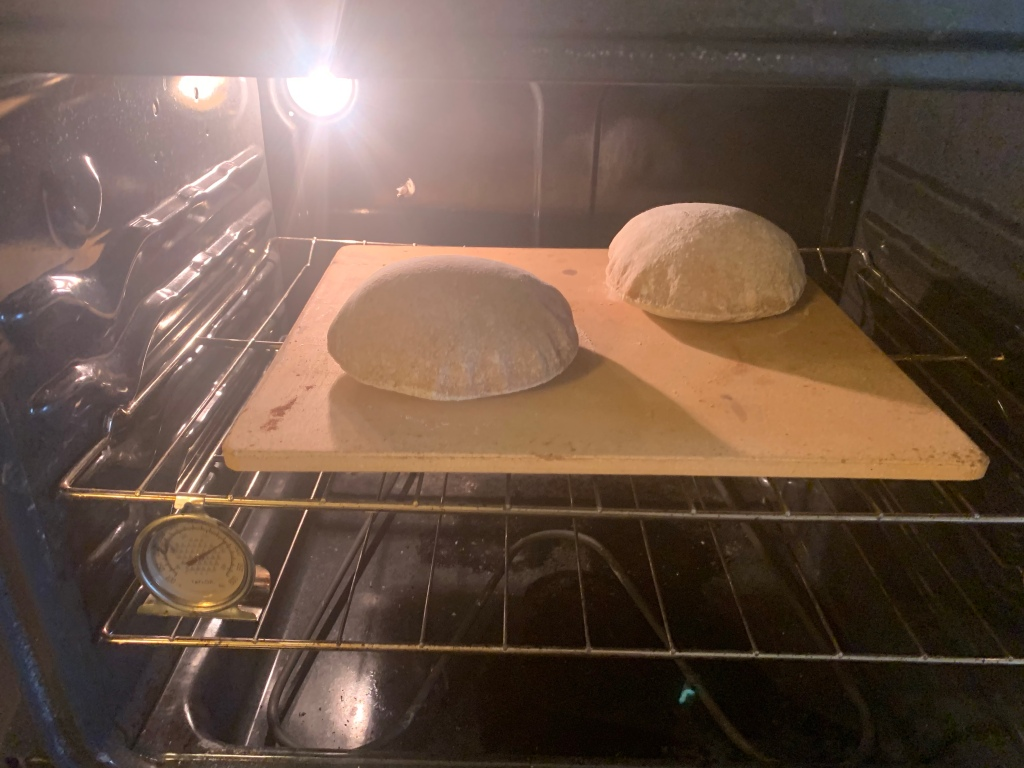 two ballooned pitas on a baking stone in an oven.