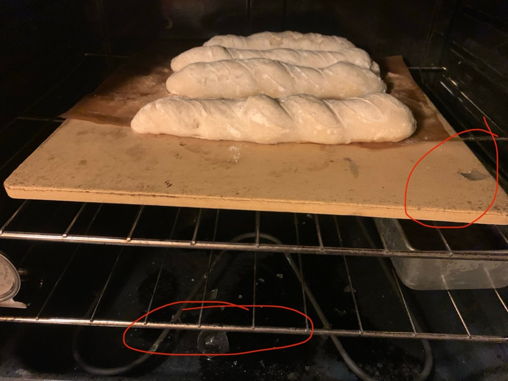 Large baking stone on the top rack of a dark oven, topped with four underbaked demibaguettes. On the baking stone and on the floor of the oven are pieces of broken glass, two of which are circled in red.