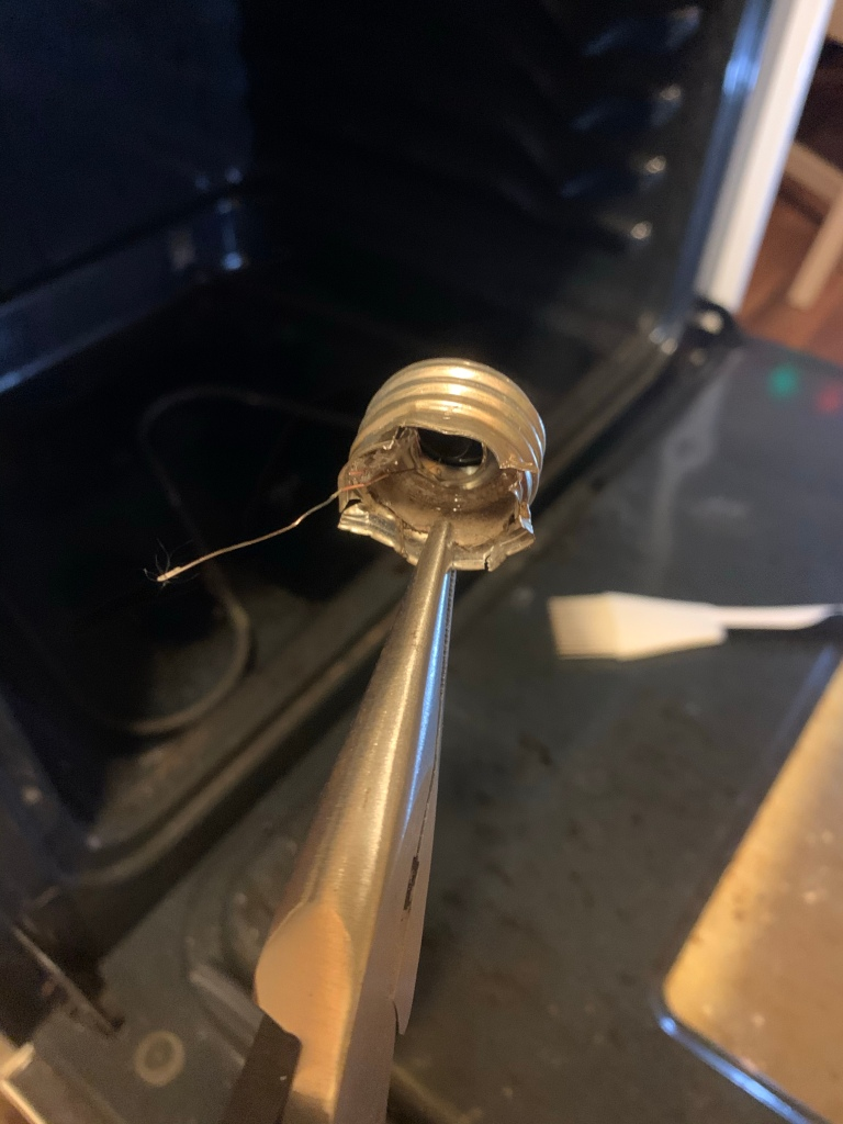 Pliers hold a mangled metal lightbulb socket in front of an open oven.