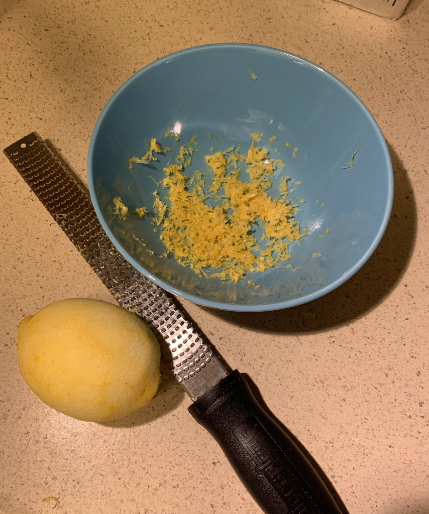 Blue bowl with fresh lemon zest on counter next to a microplane grater and a grated whole lemon.