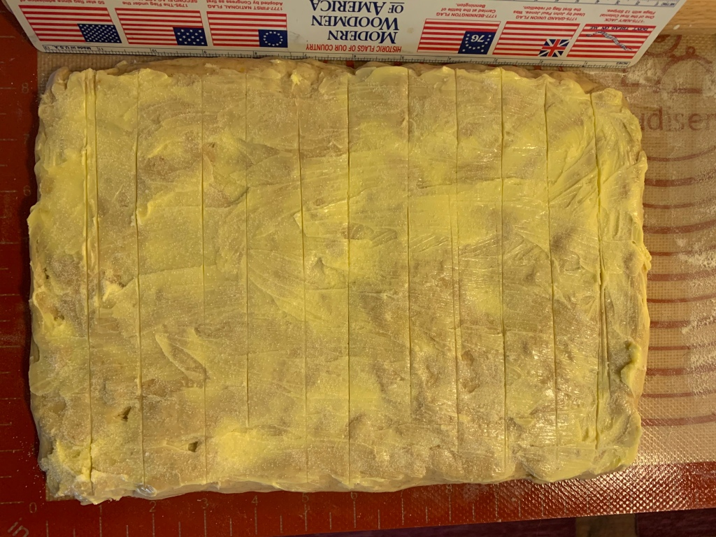 "Rectangle of dough, smeared with butter and sugar, and showing eleven roughly parallel verticle lines. Beneath is a rubber mat with an embebbed ruler. Above is an actual plastic ruler with six ""historic flags of our country,"" i.e., six versions of the U.S. flag. It reads ""Modern Woodmen of America."""