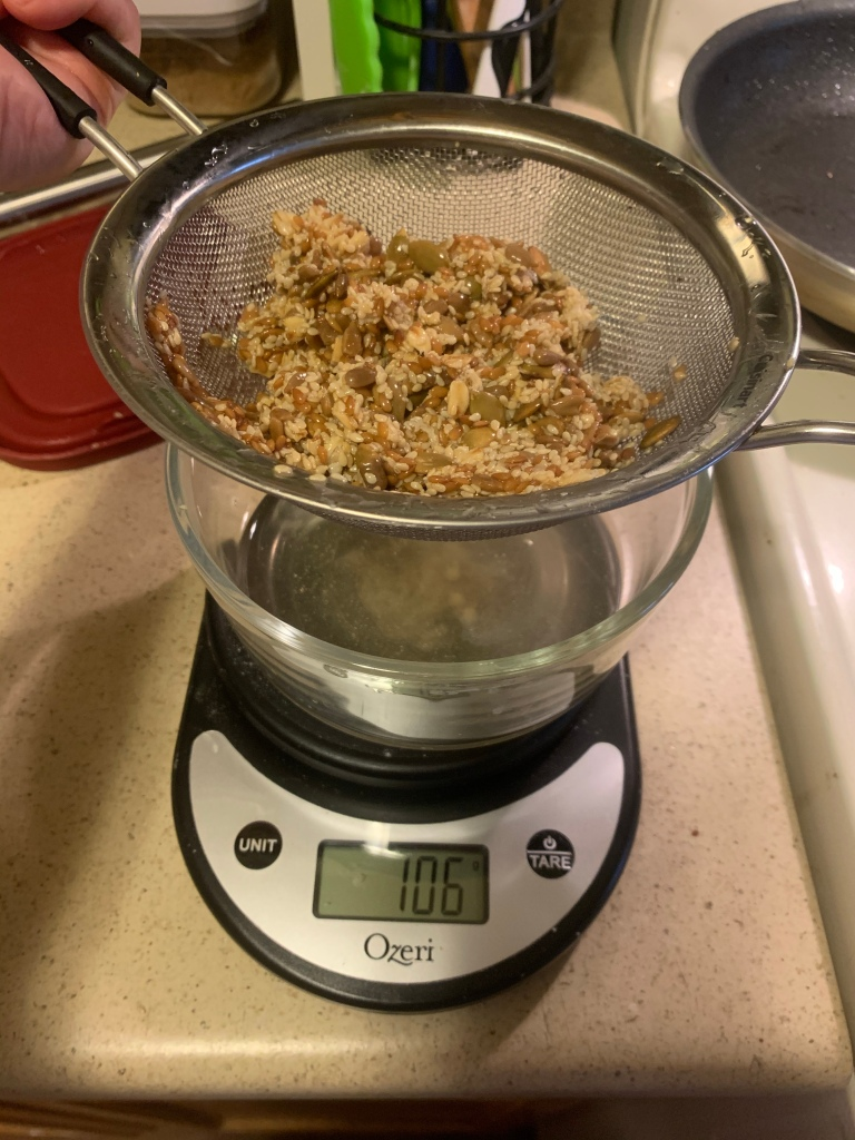 Kitchen scale on the counter reading 106g. On it is a glass bowl with liquid. Above the bowl a hand holds a strainer full of wet seeds.