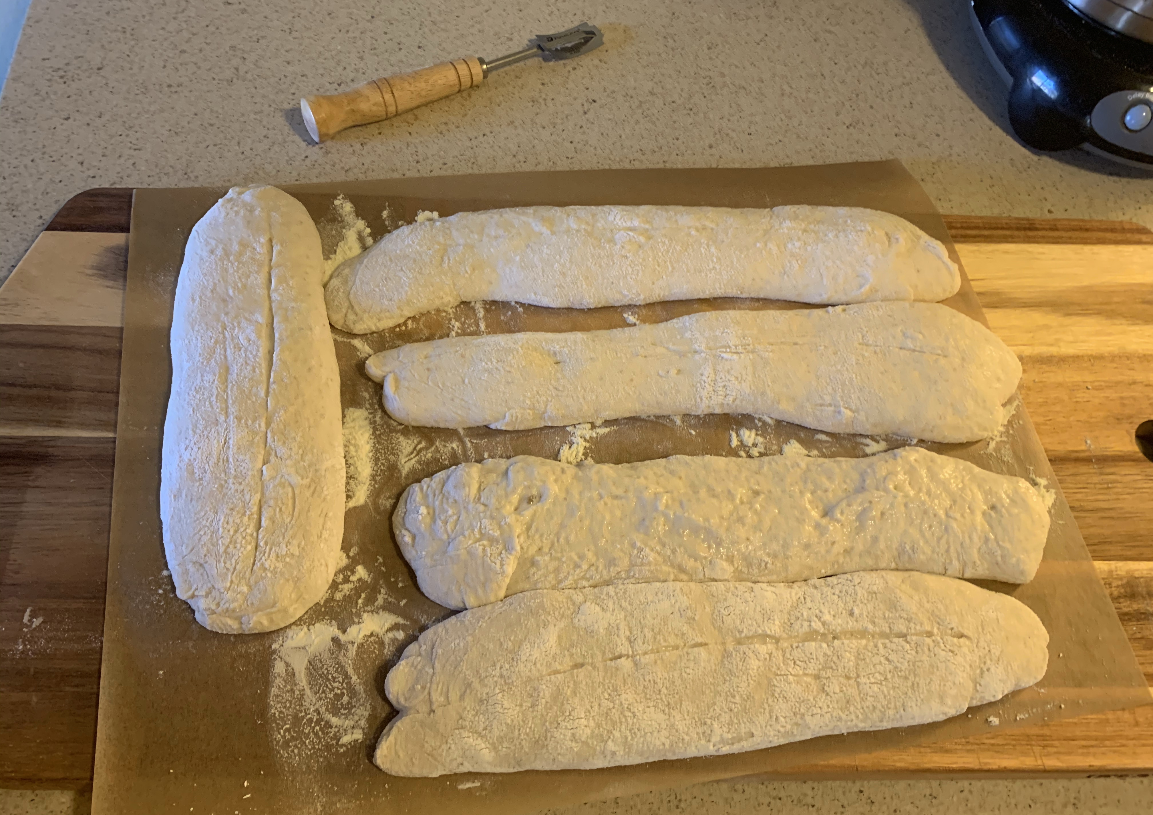 Five loaves of unbaked birote dough on a cutting board. They have been scored and the lame is on the counter near them.