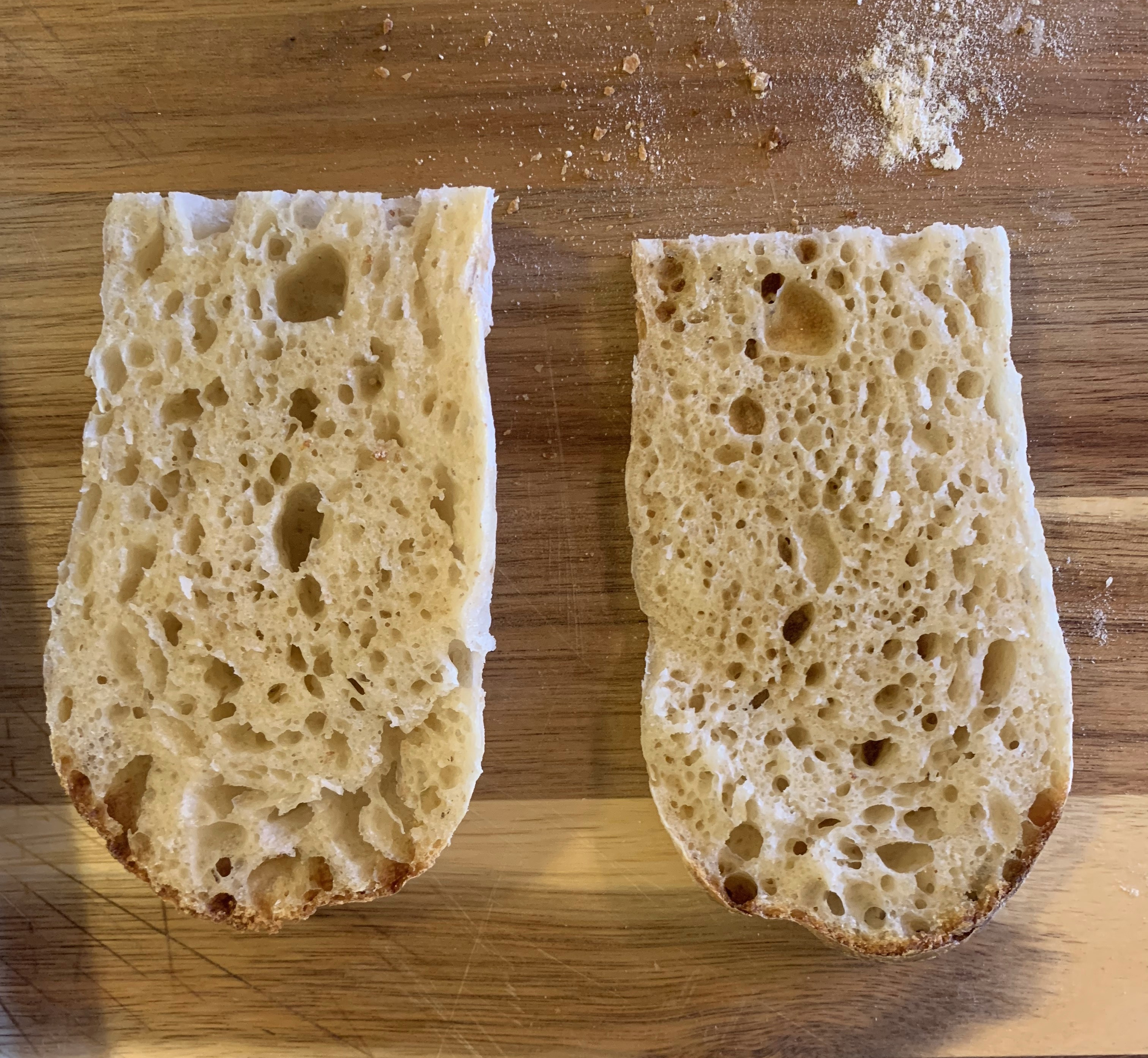 Two small pieces of birote, sliced open showing an even, medium crumb.