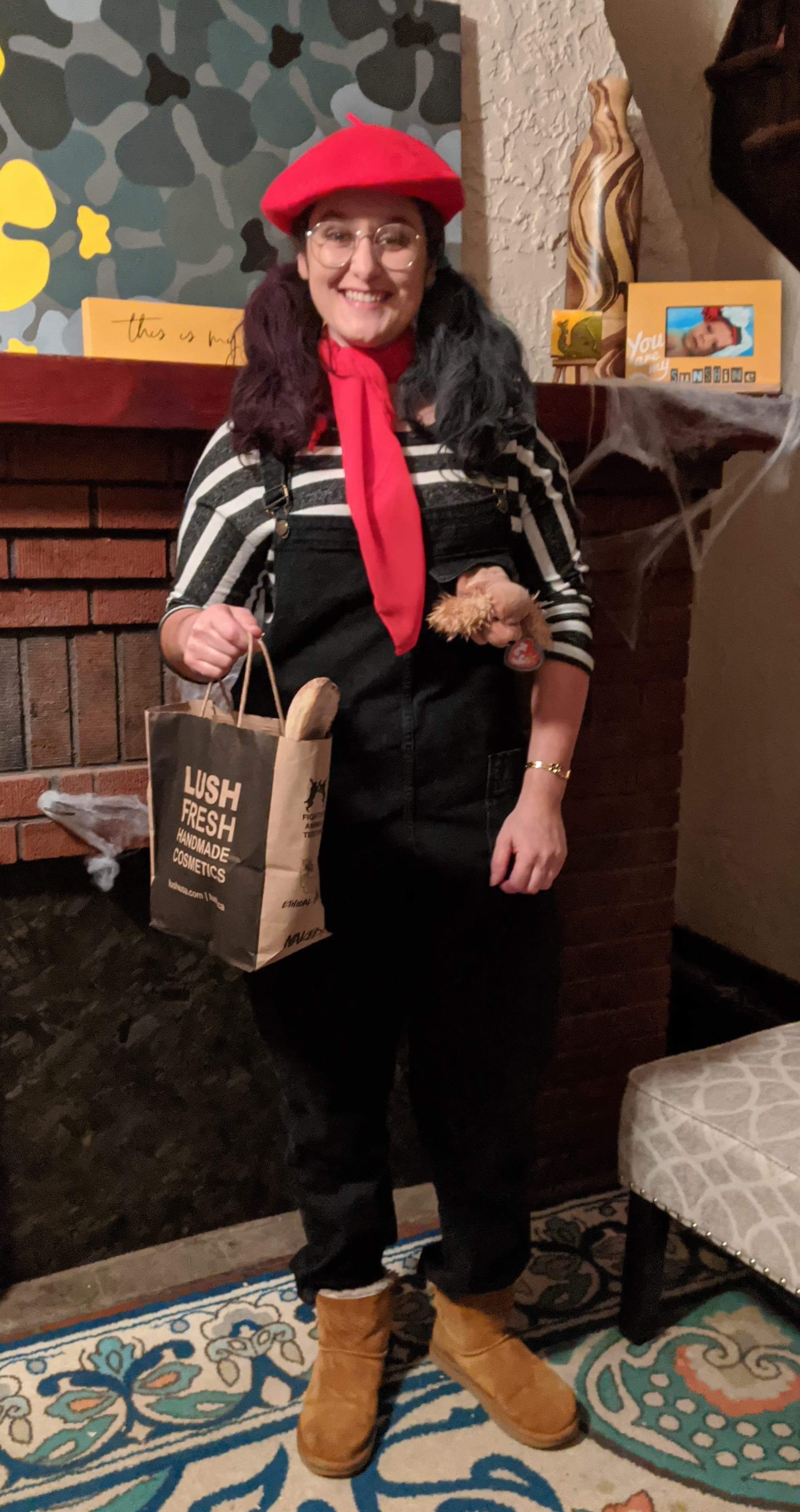 Me standing in black overalls with a red beret and scarf, holding a Lush brand paper bag with a birote sticking out. There is a cocker spaniel beanie babie in my pocket.