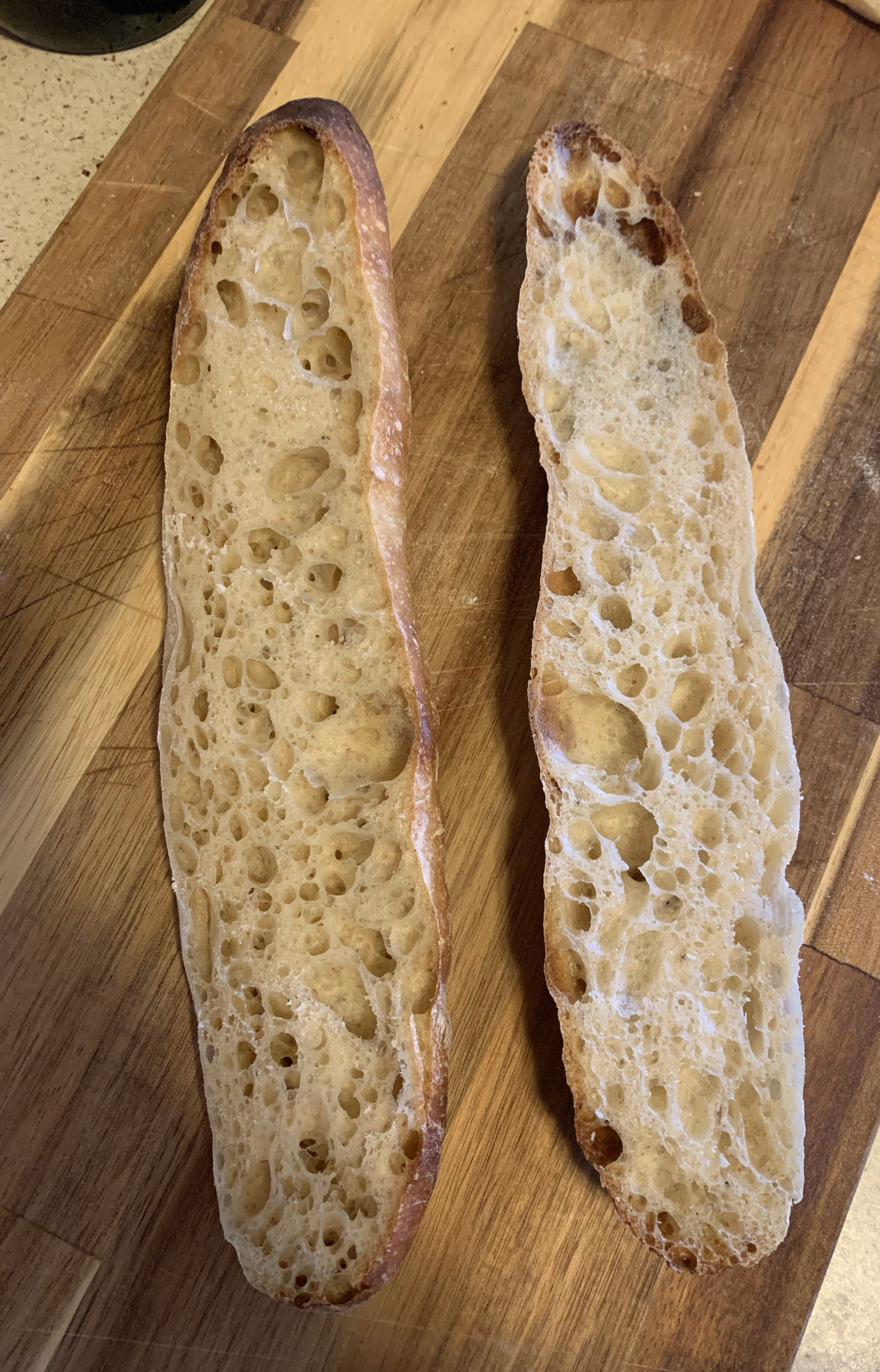 Two halves of a birote slice open, showing a big airy crumb.