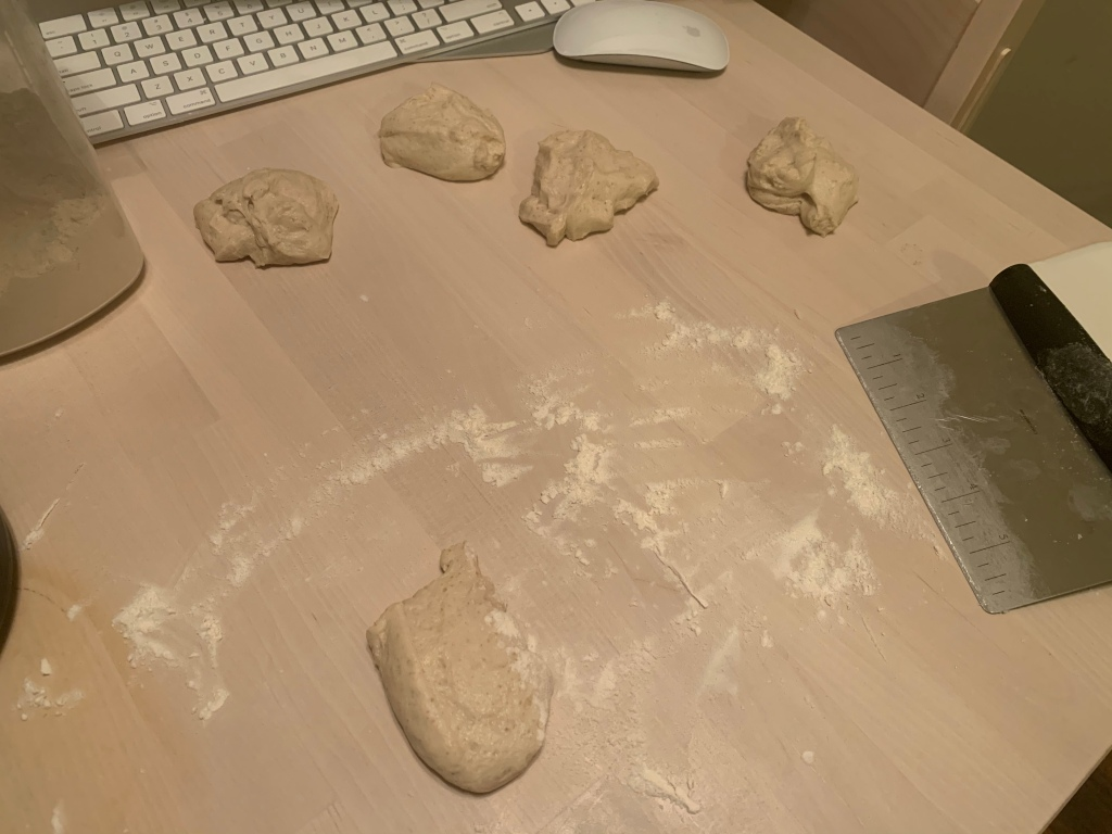 table with five unshaped blobs of dough. There is flour scattered about and a bench scraper nearby.