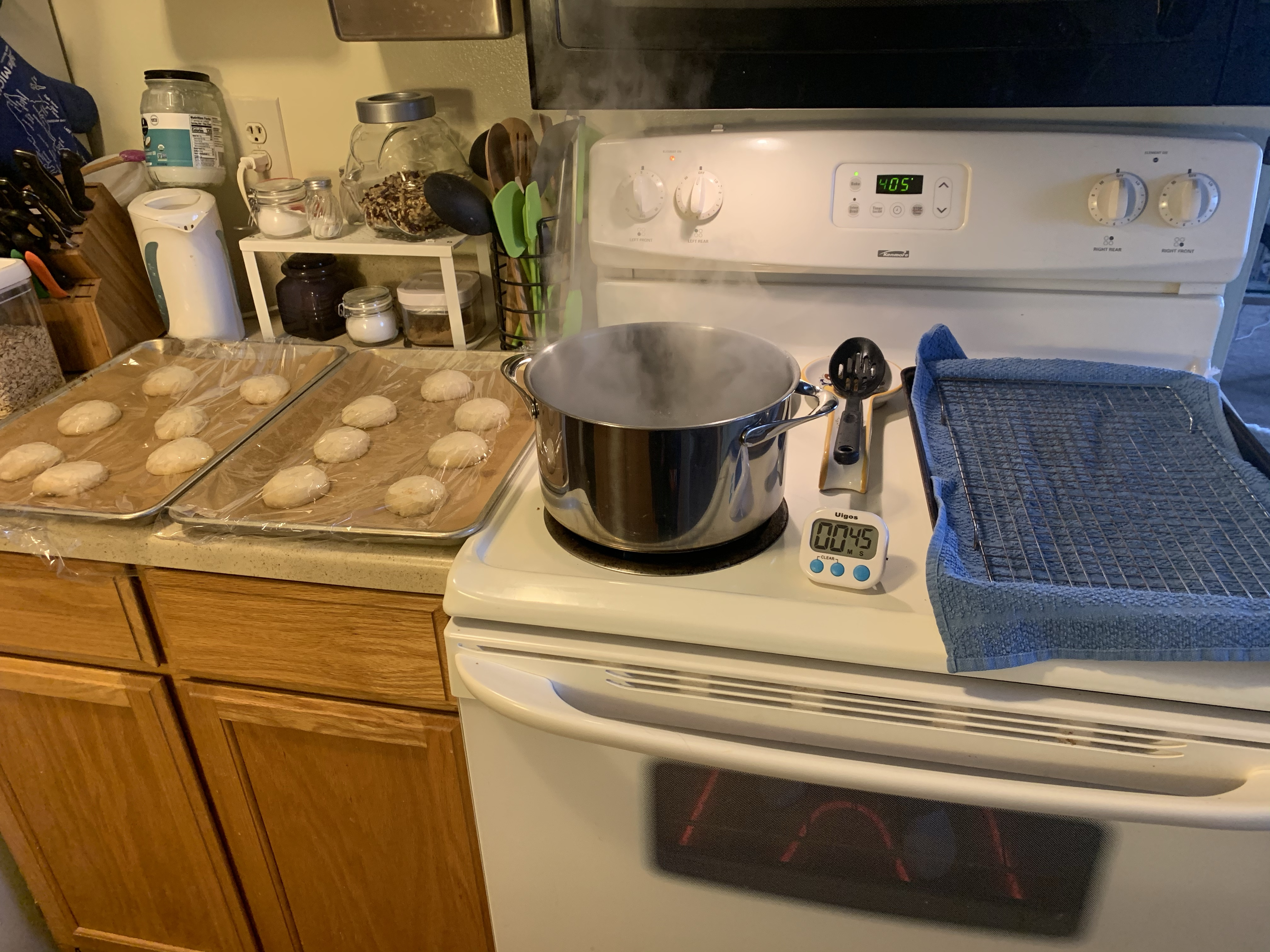 Left to right: counter with proofed rolls, still covered in cling wrap. Stove with boiling pot, timer set to 45 seconds, slotted spoon, and wire rack on on a baking tray that's lined with a towel. The oven is set to 405.
