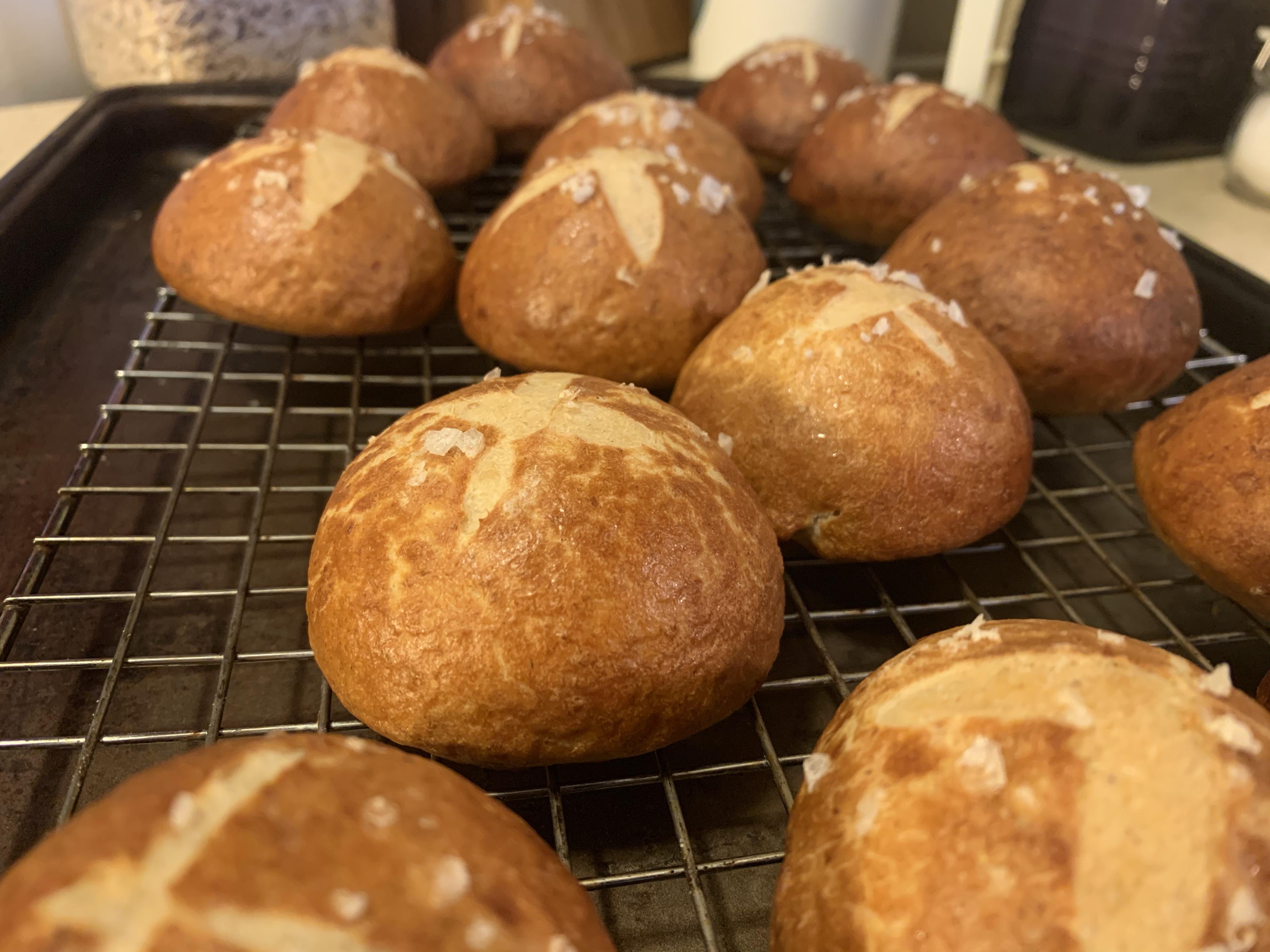 Up close shot of pretzel rolls on baking rack.
