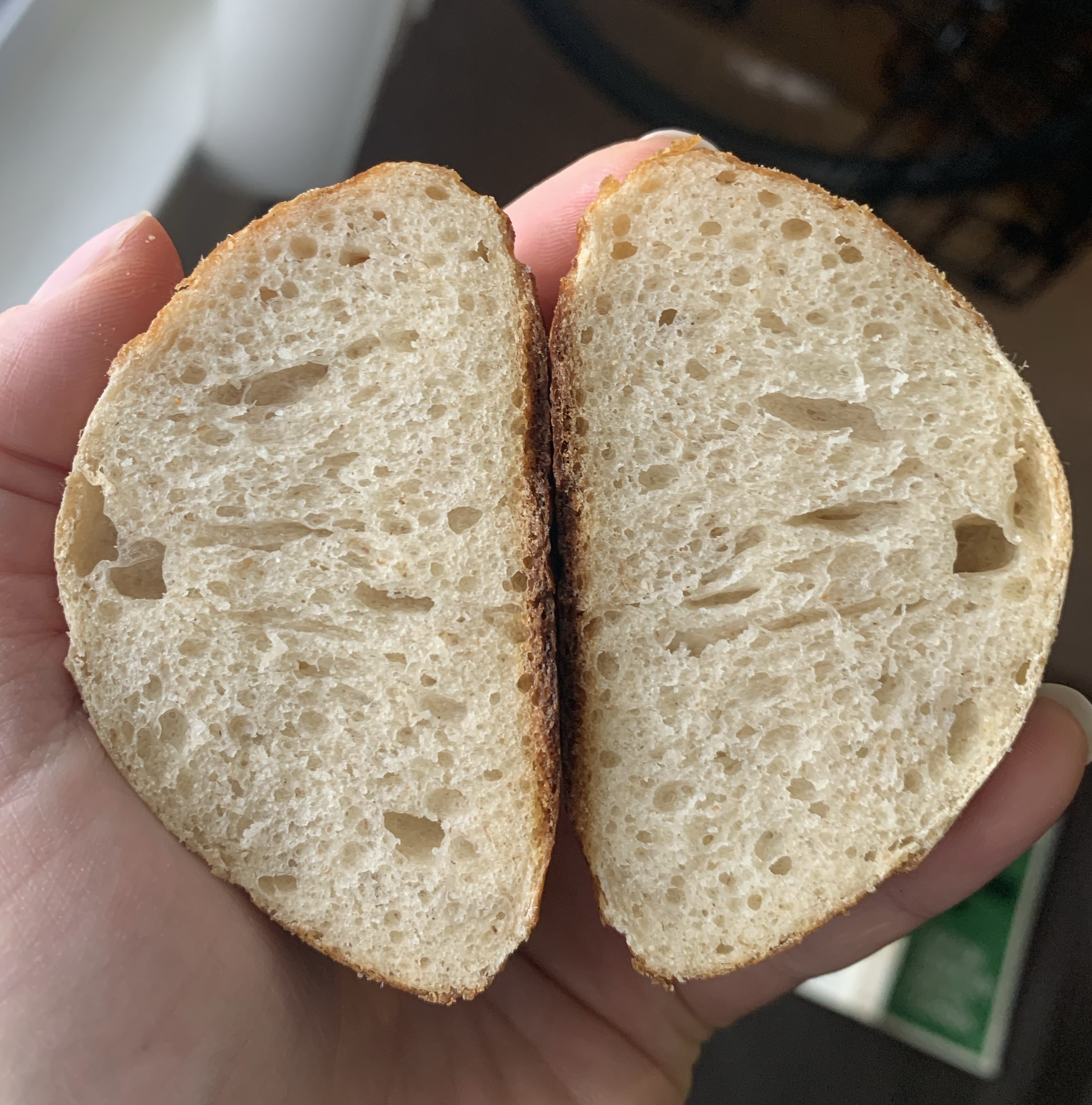 Hand holds both halves of a pretzel roll, showing the airy crumb inside.